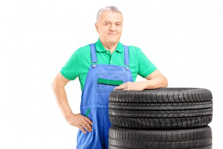 Worker posing on car tires
