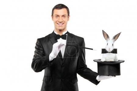 Photo pour Un magicien en costume noir tenant un chapeau haut de forme avec un lapin isolé sur fond blanc - image libre de droit