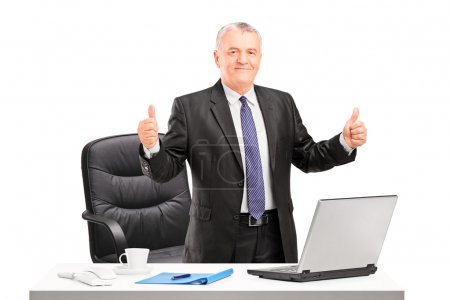 Businessman standing and giving thumbs up