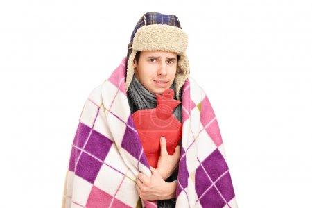 Photo pour Malade recouvert d'une couverture tenant une bouteille d'eau chaude isolée sur fond blanc - image libre de droit