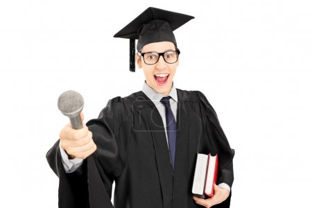 Man in graduation gown holding a microphone