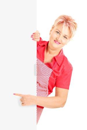 Photo pour Femme blonde souriante portant un tablier et faisant un geste sur un panneau blanc isolé sur fond blanc - image libre de droit