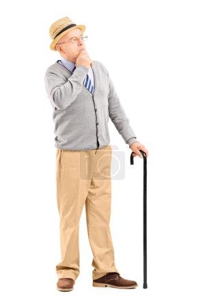 Doubtful senior man with cane