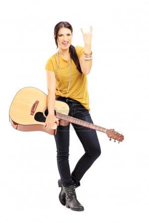 Photo pour Portrait de toute la longueur d'une jeune femme tenant une guitare acoustique et de donner un signe de rock and roll, isolé sur fond blanc - image libre de droit