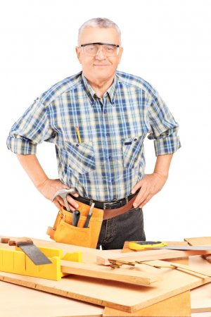 Male carpenter standing behind working table