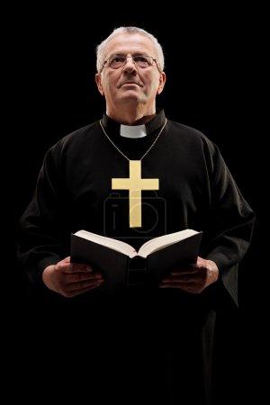 Katholischer Pfarrer hält Bibel in der Hand