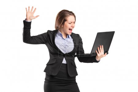Furious businesswoman yelling at laptop