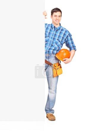 Photo pour Ouvrier de la construction debout derrière un panneau blanc isolé sur fond blanc - image libre de droit
