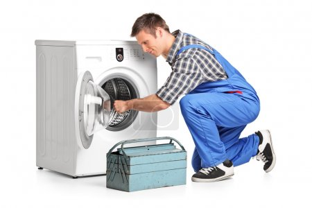 Photo for Young plumber fixing a washing machine isolated on white background - Royalty Free Image