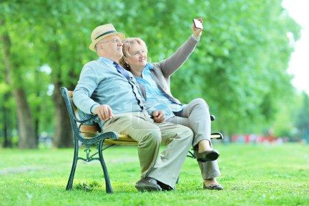 Photo pour Mature mari et femme prendre selfies dans le parc assis sur un banc en bois - image libre de droit
