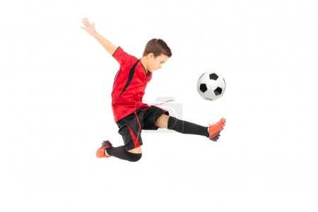 Photo for Junior football player kicking a ball isolated on white background - Royalty Free Image
