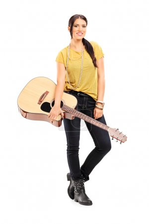 Photo for Full length portrait of a female musician holding an acoustic guitar isolated on white background - Royalty Free Image
