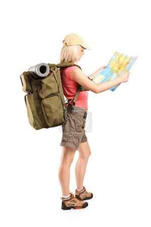 Photo pour Photo de profil d'une touriste regardant une carte isolée sur fond blanc - image libre de droit