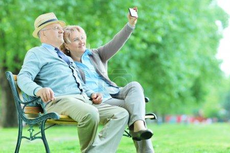 Photo pour Couple âgé prenant un selfie dans le parc assis sur un banc - image libre de droit