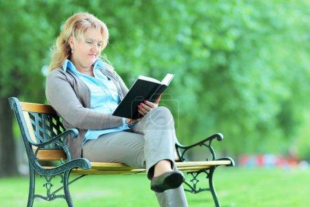 Photo pour Femme mûre lisant un livre dans un parc assis sur un banc - image libre de droit