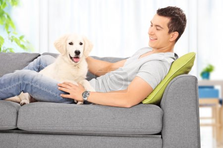 Man with puppy on sofa