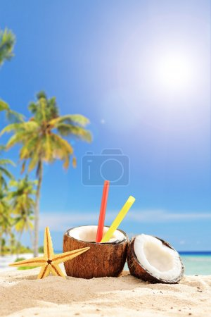Photo for Creative cocktail in a coconut cup on a tropical beach on a hot summer day - Royalty Free Image
