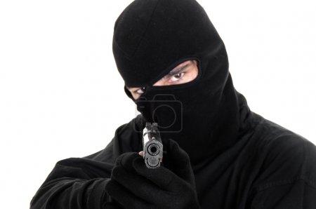 Masked man aims with gun , selective focus...