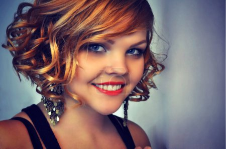 Smiling beautiful young woman with curly short red hair, red lipstick and evening make-up wearing big sparkling earrings.
