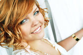 Close-up portrait of a happy smiling beautiful young woman with short curly red hair and bright blue eyes standing by the window between white lace curtains.