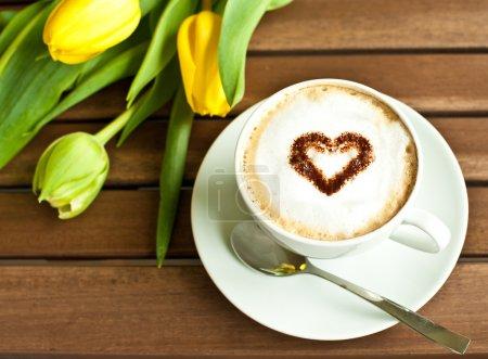 Photo pour Tasse à café avec coeur et tulipes jaunes - image libre de droit