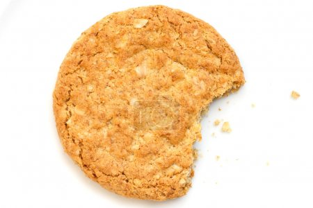 Photo for Single golden oat biscuit with a bite missing. Shot from above - Royalty Free Image