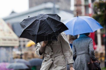 Photo pour Femme avec parapluie marchant dans la ville alors qu'il pleut abondamment - image libre de droit