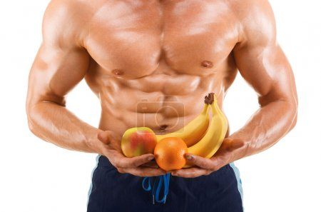 Muscular man holding a fresh fruits shaped abdominal, isolated on white background, colored retouched