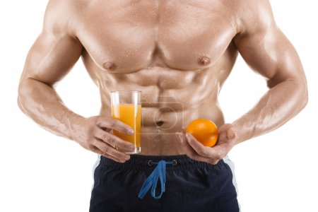 Muscular man holding a glass with juice and orange, shaped abdominal, isolated on white background