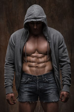 Young muscular man with open jacket revealing muscular chest and abs.