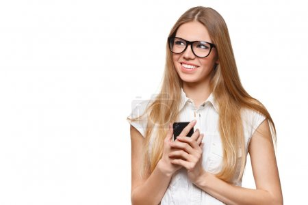 Photo pour Heureuse femme souriante tenant un téléphone portable regardant loin isolé sur fond blanc - image libre de droit