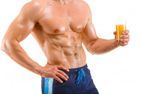 Healthy muscular man holding a glass with juice, shaped abdominal