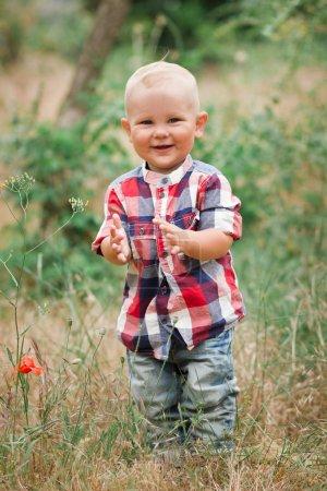 Photo pour Mode bébé garçon portant chemise à carreaux marche dans l'herbe - image libre de droit