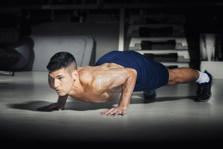 Muscular man doing push ups at gym