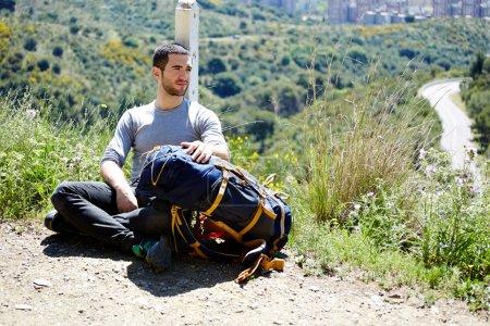 Photo pour Dans la haute montagne, le voyageur assis se reposant après le long chemin - image libre de droit
