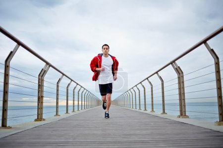 Young athlete man in white t-shirt and sports a red windbreaker runs beach pier