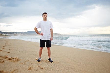 Young athlete man standing on the sand in the beach and looking away
