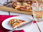 Pizza slices on a plate,  table and a glass of soda