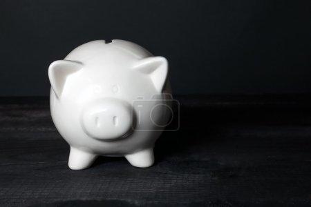 Photo pour Tirelire cochon sur fond en bois noir. Tirelire cochon en céramique pour les économies d'argent, sécurité financière ou d'un concept de fonds personnels. - image libre de droit