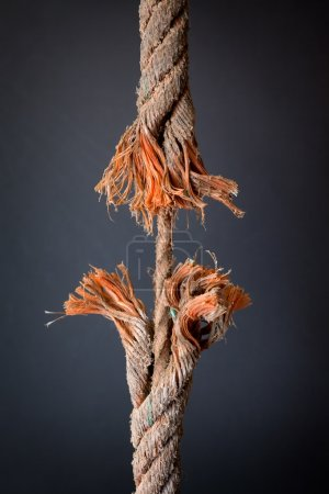 Photo for Cut and frayed rope hanging by a thread and ready to break on dark background - Royalty Free Image