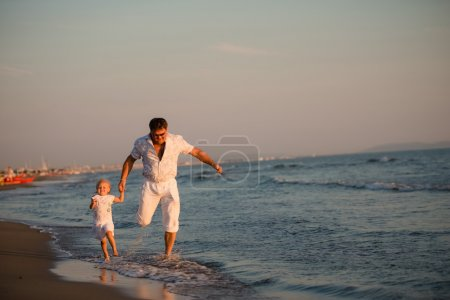 Happy father running with his daughter by the seaside at sunset,