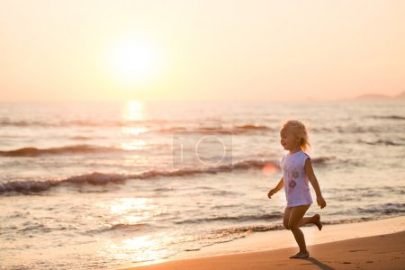 Beautiful little girl running on a beach at sunset, Italy, Forte