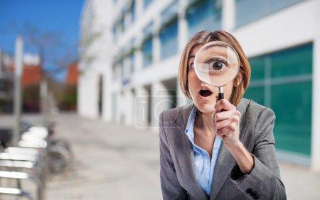Photo pour Jeune femme d'affaires regardant à travers une loupe - image libre de droit