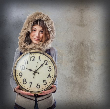 Young woman holding clock