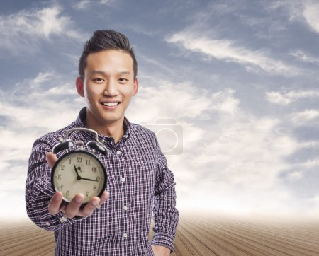 Photo for Portrait of young asian man holding an alarm clock - Royalty Free Image