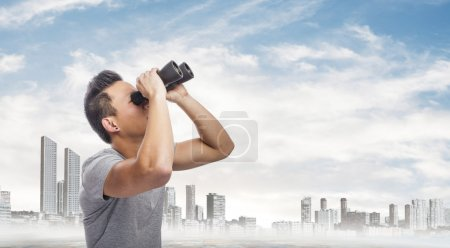 Photo for Handsome young asian man looking through binoculars - Royalty Free Image