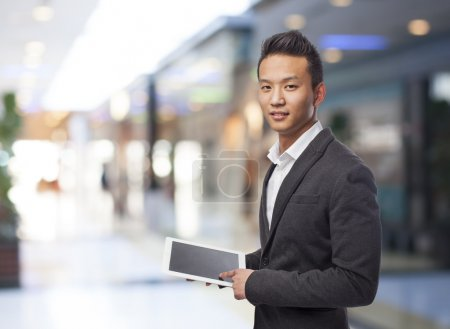 Photo for Young asian business man using his tablet - Royalty Free Image