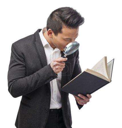 Photo pour Jeune homme d'affaires asiatique regardant à travers la loupe - image libre de droit