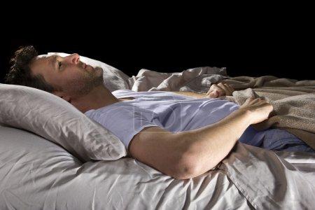 Photo pour Gros plan d'insomniaque incapable de dormir dans son lit - image libre de droit