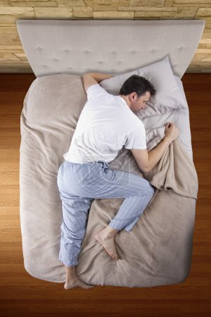 Photo for Top view of bedroom with insomniac man unable to sleep - Royalty Free Image